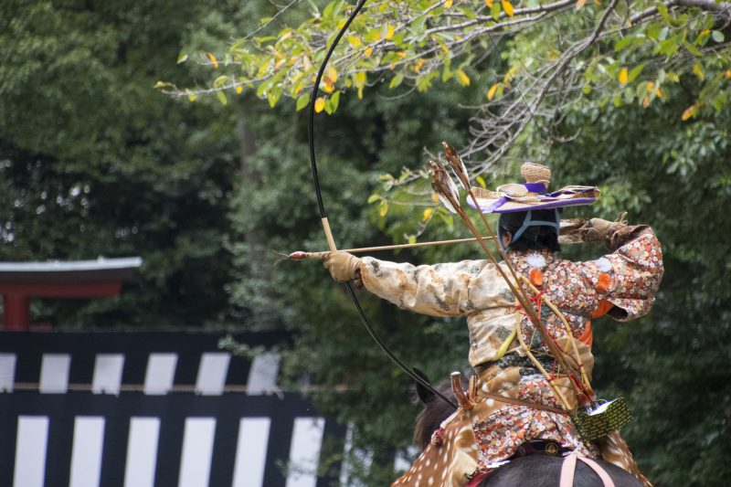 An archer dressed in samurai hunting garb takes aim