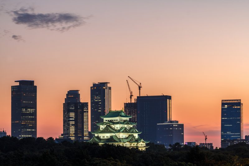 Nagoya Castle is lit up beautifully among Nagoya's buildings in the evening